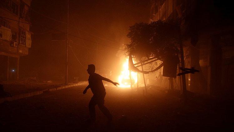 Un hombre corre frente a un coche en llamas tras un ataque aéreo contra la ciudad de Duma, situada al este de Damasco.