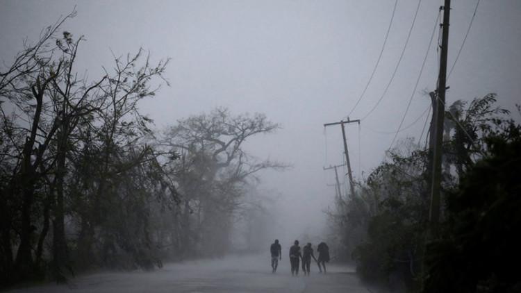 La gente camina por una carretera en pleno paso del huracán Matthew bajo un aguacero en Les Cayes (Haití).