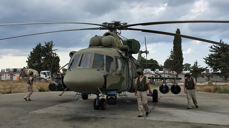 Varios pilotos inspeccionan un helicóptero de transporte y ataque Mi-8AMSht en la base aérea de Jmeimim, Siria.
