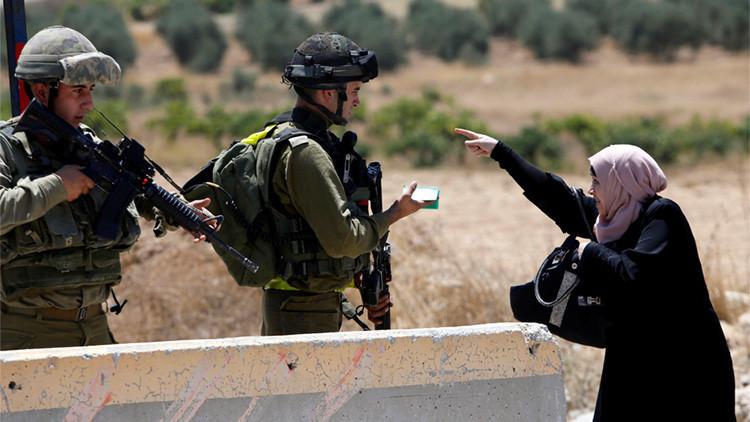 Una mujer palestina discute con soldados israelíes en un puesto de control durante enfrentamientos en el campamento de Fawwar, al sur de Hebrón, el 16 de agosto de 2016.