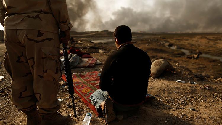 Un soldado iraquí se encuentra al lado de un hombre detenido, acusado de ser un miembro del Estado Islámico, en un punto de control en Qayyara, al sur de Mosul (Irak)