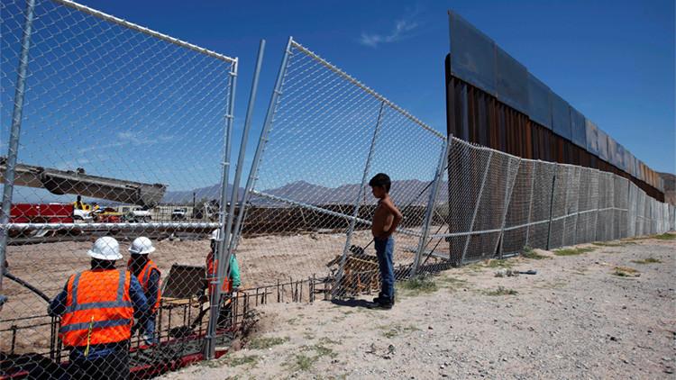 Un niño mira a los trabajadores estadounidenses que construyen una sección del muro de la frontera EE.UU.-México,  frente a la ciudad fronteriza mexicana de Ciudad Juárez. Fotografía tomada desde el lado de la frontera México EE.UU.-México. REUTERS / José Luis González