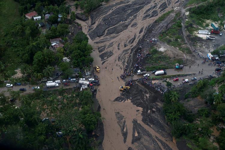 Varios haitianos contemplan un puente que destrozó el huracán Matthew en Petit Goâve, Haití, 5 de octubre de 2016.