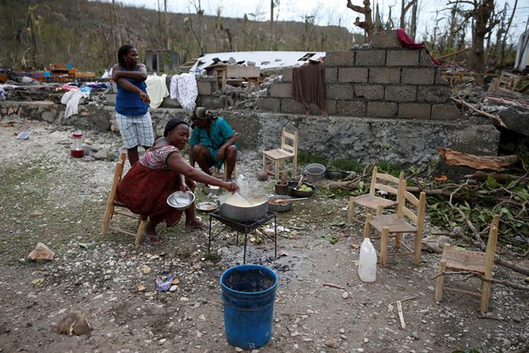 Varias mujeres cocinan en una escuela parcialmente destruida que emplean como refugio tras el paso del huracán Matthew, Jérémie, Haití, 5 de octubre de 2016.