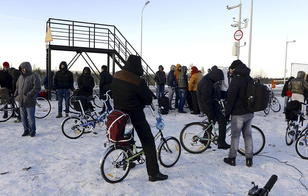 Refugiados y migrantes se reúnen cerca de un puesto de control de la frontera rusonoruega a las afueras de Níkel, región de Murmansk, Rusia, 30 de octubre de 2015