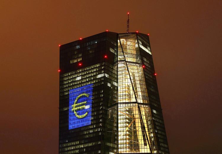 Sede del Banco Central Europeo iluminada con una imagen gigante del euro