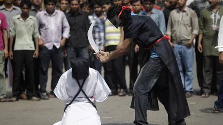 Miembros del Movimiento Mágico, un grupo de jóvenes de Bangladés, imitan una escena de ejecución en una protesta contra la ejecución por parte de  Arabia Saudita de 8 trabajadores, migrantes de Bangladés, frente del Museo Nacional en Daca, el 15 de octubre de 2011