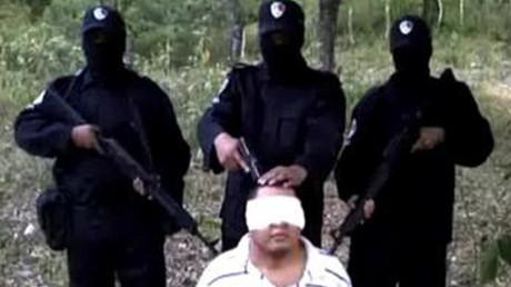 Miembros armados de Los Zetas interrogan a un miembro del Cártel del Golfo