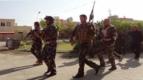 Miembros de las Fuerzas Kurdas patrullan por una calle en Kirkuk, Irak, el 22 de octubre de 2016.