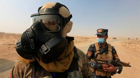 Tropas iraquíes llevan máscaras protectoras para protegerse del humo de una planta de azufre quemada por los terroristas del Estado Islámico en el sur del Distrito de Mosul en Qayara, Irak, el 22 de octubre de 2016.