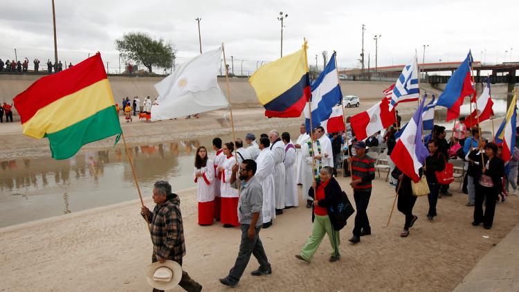 Personas con banderas en el lado mexicano de la valla fronteriza entre Ciudad Juárez (México) y El Paso (EE.UU.), durante una manifestación en apoyo de los migrantes