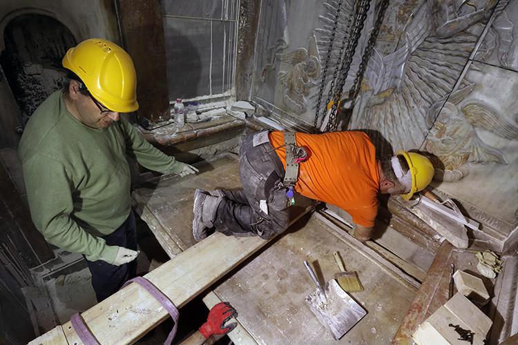 Expertos griegos en conservación de patrimonio cultural colocan la lápida de mármol que cubría la tumba de Jesucristo en la iglesia del Santo Sepulcro en Jerusalén, el 28 de octubre de 2016.