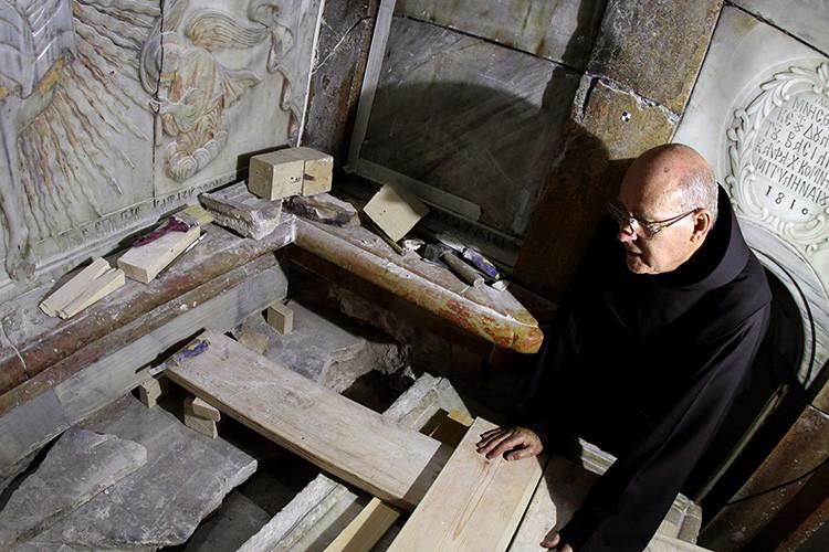 Un fraile franciscano observa la tumba expuesta en la que se cree que fue sepultado el cuerpo de Jesús. Allí un equipo griego de preservación realiza trabajos de conservación. Jerusalén, Israel, 28 de octubre de 2016.