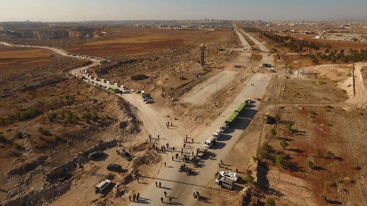 Miembros de las fuerzas de seguridad junto a autobuses y ambulancias cerca de un corredor humanitario en la carretera de Castello, en el norte de Alepo, Siria, el 20 de octubre de 2016.