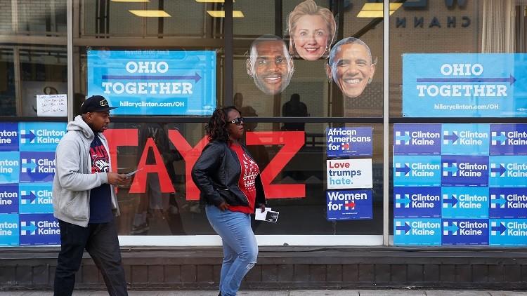 Varias personas pasan junto a un establecimiento que distribuye entradas para un concierto de apoyo a la candidata demócrata a la presidencia de EE.UU., Hillary Clinton, en Cleveland, Ohio, EE.UU., el 29 de octubre de 2016.