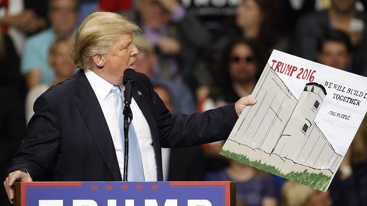 El aspirante republicano a la Casa Blanca, Donald Trump, sostiene un dibujo del muro que planea construir entre EE.UU. y México, el 10 de marzo de 2016.
