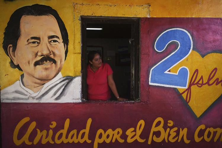 Una mujer se asoma de la ventana del edificio con imágenes del presidente de Nicaragua, Daniel Ortega, y su esposa Rosario Murillo en la ciudad nicaragüense de Masaya, el 3 de noviembre de 2016.