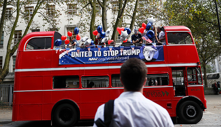 Un activista ata banderas estadounidenses a un autobús con la leyenda 'Stop Trump' antes de viajar por Londres para instar a los estadounidenses residentes en la capital del Reino Unido a registrarse y votar en las presidenciales, el 21 de septiembre de 2016.