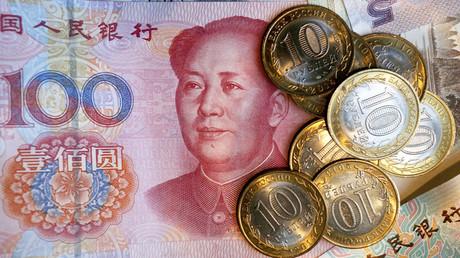 Un billete chino de 100 yuanes y monedas rusas de 10 rublos