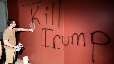 Un hombre trata de remover un grafiti que reza 'Kill Trump' (Mata a Trump), durante una protesta en Oakland (California, EE.UU.), el 9 de noviembre de 2016.