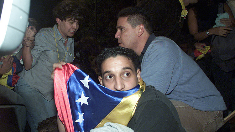 Manifestantes se esconden de los disparos de João de Gouveia, en Caracas el 6 de diciembre de 2002.