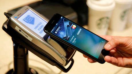 Un hombre efectua un pago electrónico con su smartphone