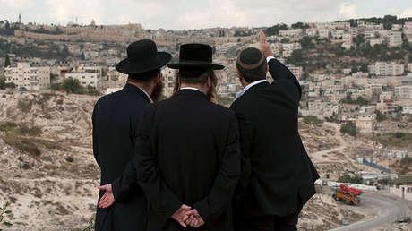Tres hombres contemplan la ciudad vieja de Jerusalén