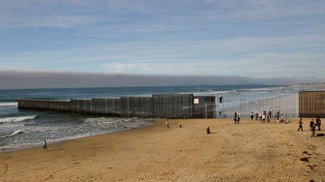 La gente se apuesta cerca de un muro que separa a México y Estados Unidos, mientras un artista pinta parte de él desde Playas Tijuana, México. 10 de diciembre de 2016.