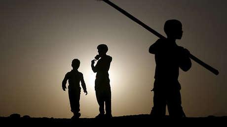 Niños juegan en una colina en Kabul al anochecer. 23 de abril de 2015
