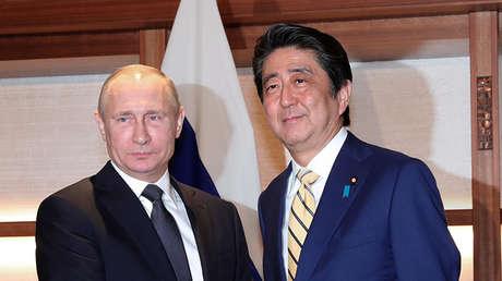 El presidente ruso, Vladímir Putin (izquierda), con el primer ministro de Japón, Shinzo Abe (derecha)