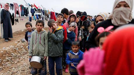 Gente que logró escapar de la ciudad de Mosul, se alinea para recibir comida en un campo de refugiados, Irak, 18 de diciembre de 2016