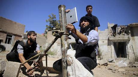 Un integrante de la brigada Ansar Dimachk, miembro del Ejército Sirio Libre que lucha contra las fuerzas del Gobierno, utiliza un iPad durante un combate en el distrito de Jobar. 15 de septiembre de 2013.