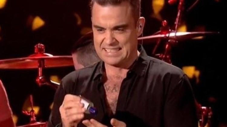 Robbie Williams se desinfecta las manos con cara de 'asco' tras tocar a sus fans