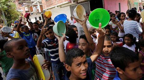 Fila de niños que esperan recibir comida gratis preparada por habitantes y voluntarios en una calle cerca de Caucagüita, en Caracas. Venezuela