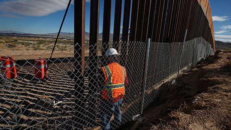 Un obrero trabajando en la construcción del muro fronterizo entre México y EE.UU.