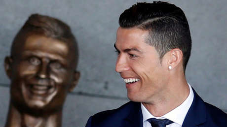 Cristiano Ronaldo sonriendo junto a su busto