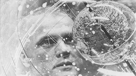 John H. Glenn, el primer astronauta estadounidense que orbitó la Tierra, observa un Dispositivo de Entrenamiento Celestial (globo terráqueo) antes de su vuelo.