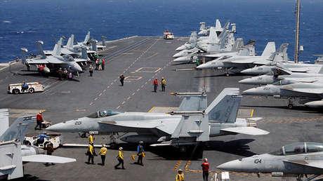 Personal de la Marina estadounidense preparándose para el despegue de un avión de combate F18 desde la cubierta del portaaviones USS Carl Vinson.