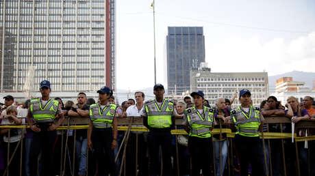 Varios agentes de la Policía hacen guardia frente a una iglesia de Caracas, Venezuela.