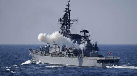El destructor Shimakaze de la Fuerza Naval de Autodefensa de Japón disparando cañones durante un desfile