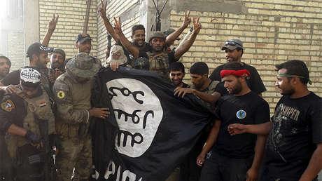 Fuerzas de seguridad iraquíes retiran la bandera del Estado Islámico de una universidad en la provincia de Anbar, Irak, el 26 de Julio de 2015.