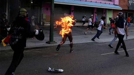 Un hombre al que prendieron fuego camina envuelto en llamas por Caracas, Venezuela, durante las protestas de la oposición contra el presidente del país, Nicolas Maduro, el 20 de mayo de 2017.
