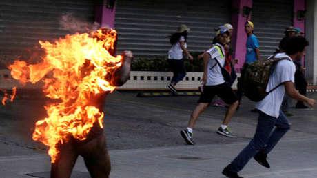 Hombre que fue incendiado por personas que lo acusaron de robar durante una manifestación contra el Presidente de Venezuela, Nicolas Maduro, corre en medio de partidarios de la oposición en Caracas, Venezuela, el 20 de mayo de 2017.