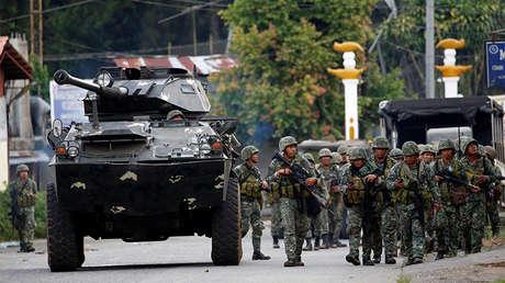 Marines filipinos caminan junto a un vehículo blindado en la ciudad de Marawi, el 28 de mayo de 2017.