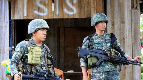 Soldados vigilan a lo largo de la calle principal del pueblo de Mapandi mientras las tropas del gobierno continúan su asalto contra los insurgentes del grupo de Maute, que se han apoderado de grandes partes de la ciudad de Marawi, Filipinas el 2 de junio de 2017.