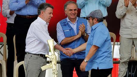 El líder de las FARC, Rodrigo Londoño; el presidente colombiano Juan Manuel Santos y el Representante Especial del Secretario General de la ONU para Colombia, Jean Arnault, asisten al acto de dejación de armas de la guerrilla. 27 de Junio de 2017.