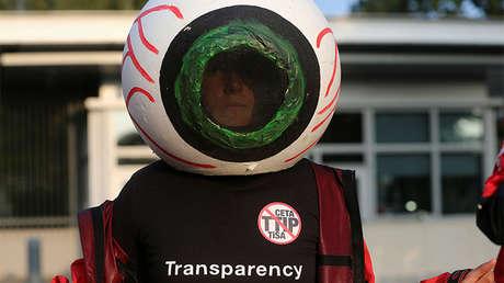 Activista de Greenpeace durante una protesta contra el TTIP, el CETA y el TISA frente a la sede de la misión de EE.UU. en Ginebra (Suiza)