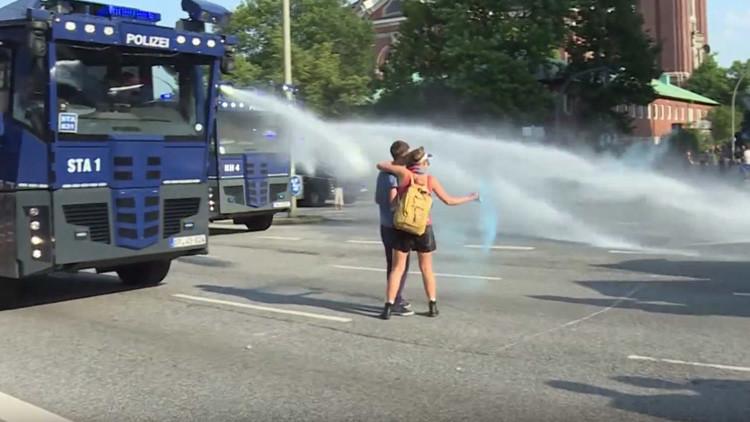 Beso anti-G20: un cañón de agua 'enfría' la pasión de una pareja en Hamburgo (VIDEO)