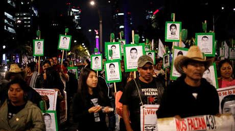 Familiares sostienen carteles con imágenes de algunos de los 43 estudiantes desaparecidos del Colegio Ayotzinapa, Raúl Isidro Burgos, en protesta para exigir justicia a los estudiantes desaparecidos en México. 6 de mayo de 2017.
