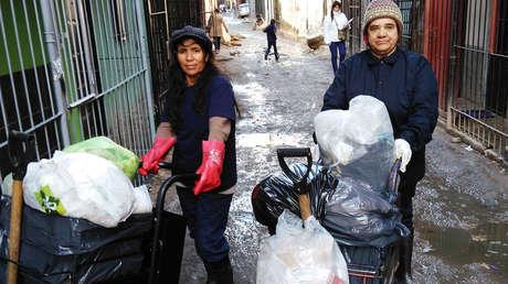 Isidora López (a la izquierda) y Claudelina Ruiz (derecha) recogen la basura de sus vecinos en el barrio San Martín de la Villa 31, Buenos Aires.